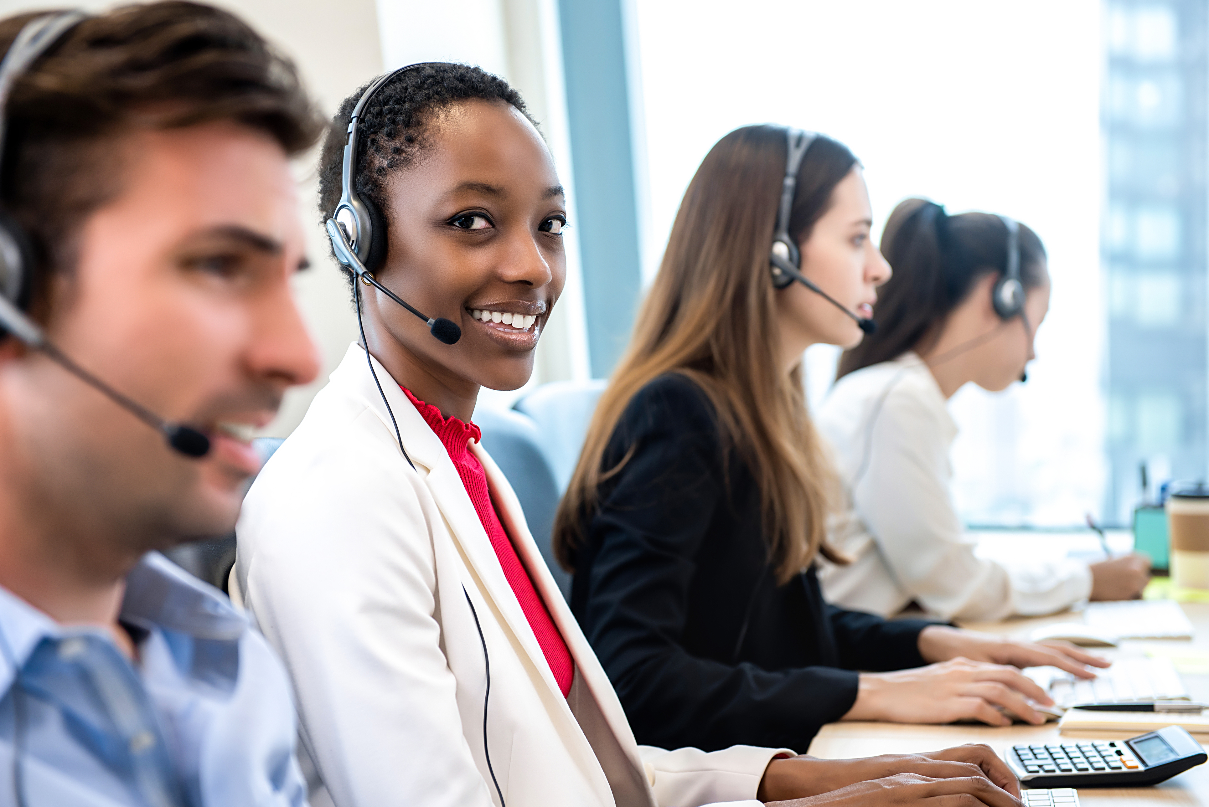 Smiling beautiful African American woman working in call center with diverse team